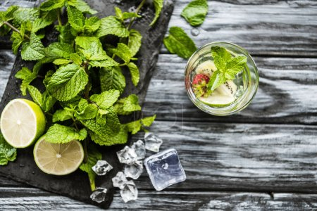 top view of glass with fresh cold strawberry and kiwi mojito on wooden table