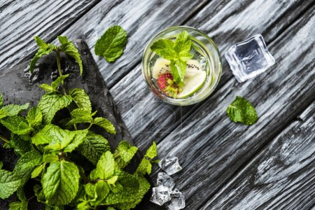 top view of fresh strawberry and kiwi mojito in glass on wooden table