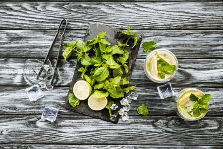 Ansicht von Minze, Limette, Eiswürfeln und Gläsern mit Mojito auf Holzoberfläche