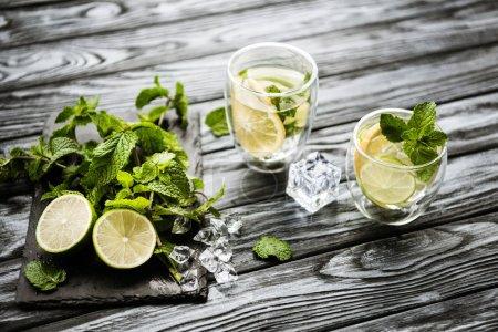 Photo pour Vue grand angle des verres avec mojito et des ingrédients frais sur la surface en bois - image libre de droit