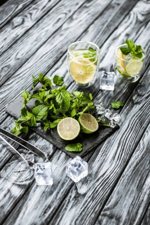 high angle view of summer cocktail in glasses and ingredients for making mojito on wooden table