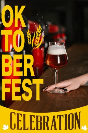 """cropped shot of human hand with glass of fresh beer in bar with """"oktoberfest celebration"""" lettering"""