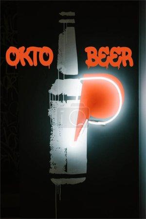 "illuminated beer bottle symbol on dark wall in pub with ""oktoberfest"" lettering"