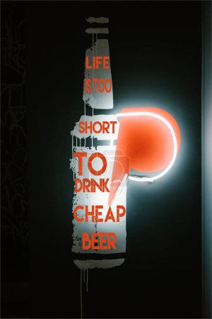 "illuminated beer bottle symbol on dark wall in pub with ""life is too short to drink cheap beer"" lettering"