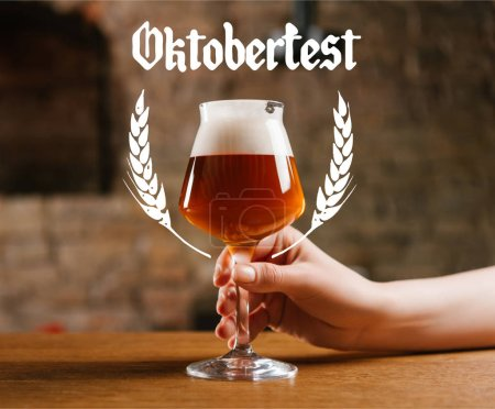 """partial view of person holding glass of fresh cold beer in pub with """"oktoberfest"""" lettering"""