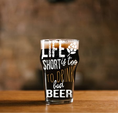 "glass of fresh cold dark beer on wooden table in pub with ""life is too short to drink cheap beer"" inspiration"