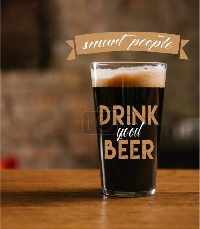 """close-up view of glass with delicious dark beer on table in pub with """"smart people drink good beer"""" inspiration"""
