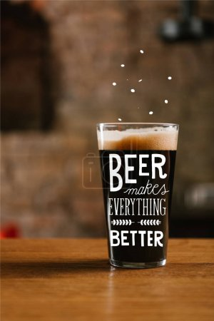 "close-up view of glass with delicious dark beer on table in pub with ""beer makes everything better"" inspiration"