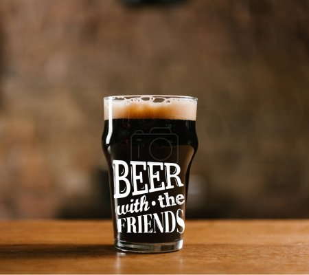 """glass of fresh cold dark beer on wooden table in pub with """"beer with the friends"""" inspiration"""