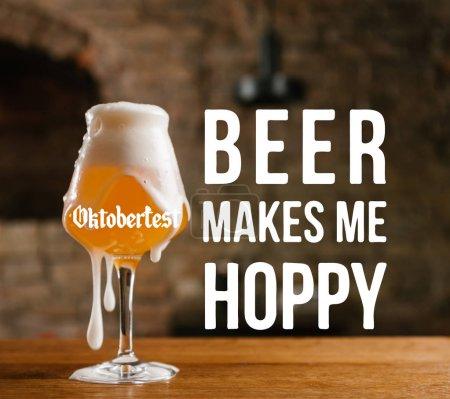 """Photo pour Vue rapprochée de bière froide avec mousse en verre sur table en bois avec l'inspiration """"oktoberfest - beer makes me hoppy"""" - image libre de droit"""