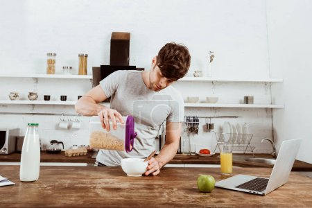 Photo for Male freelancer making breakfast with corn flakes at table with laptop in kitchen at home - Royalty Free Image
