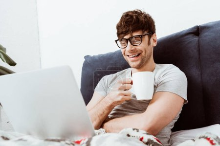 laughing male freelancer with coffee cup sitting on bed with laptop at home