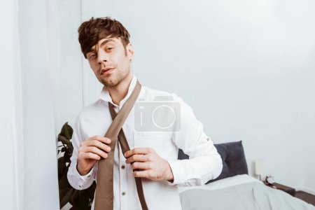 Photo for Selective focus of businessman in white shirt tying neck tie at home - Royalty Free Image