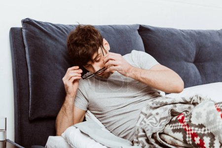 Photo for Man waking up and putting on eyeglasses during morning time in bed at home - Royalty Free Image