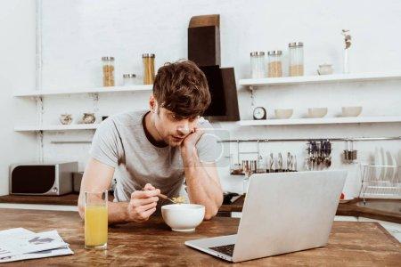 jeune freelance mâle manger des flocons de maïs sur le petit déjeuner à table avec ordinateur portable dans la cuisine à la maison
