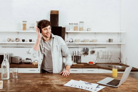 happy male freelancer in headphones standing near table with laptop in kitchen at home