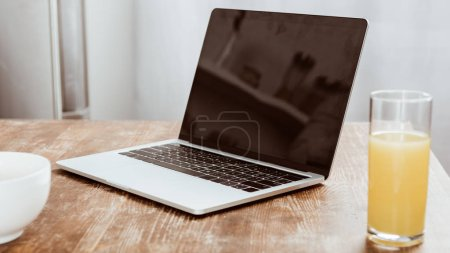 close up view of laptop with blank screen and orange juice at table