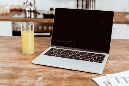 selective focus of laptop with blank screen and orange juice at table