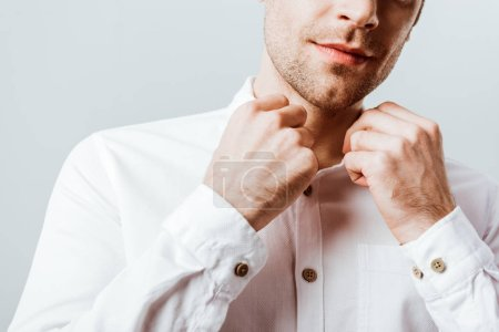 cropped image of handsome businessman buttoning up white shirt isolated on grey