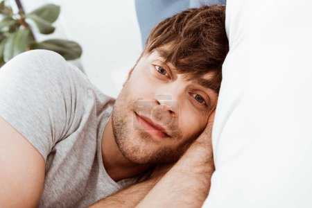Photo for Close up portrait of man looking at camera and laying in bed at home - Royalty Free Image