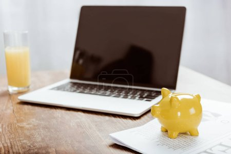 yellow piggy bank and laptop with blank screen at table