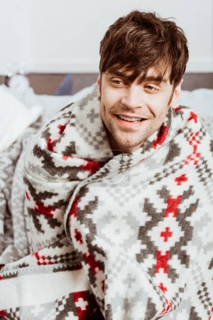 smiling sick young man wrapped in blanket sitting on bed at home
