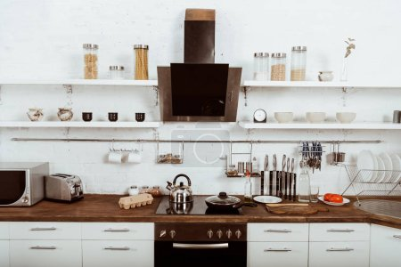 Photo for Selective focus of modern kitchen interior with frying pan and teapot on stove - Royalty Free Image