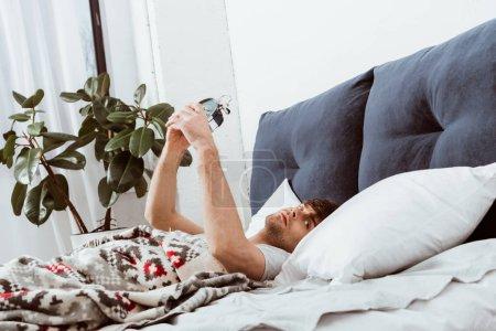 Photo pour Vue latérale du jeune homme éteignant le réveil dans le lit à la maison - image libre de droit