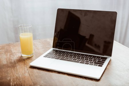 Photo for Close up view of laptop with blank screen and orange juice at table - Royalty Free Image
