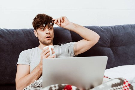 young male freelancer taking off eyeglasses and holding coffee cup on bed with laptop at home