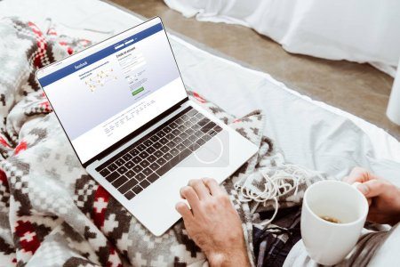 cropped image of man holding coffee cup and using laptop with facebook on screen in bed at home
