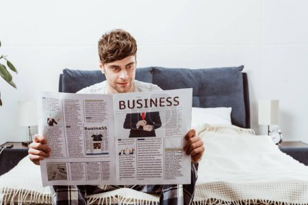 smiling man reading business newspaper on bed at home