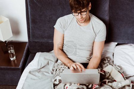 high angle view of male freelancer working on laptop in bed at home