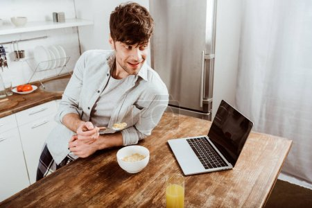 high angle view of male freelancer eating corn flakes on breakfast at table with laptop in kitchen at home