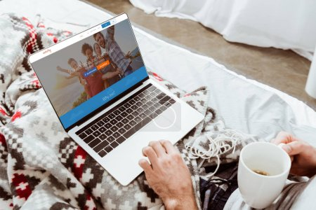 cropped image of man holding coffee cup and using laptop with couchsurfing on screen in bed at home