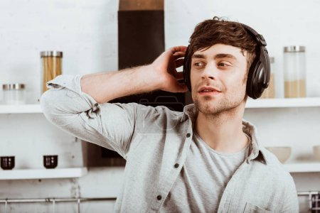 handsome man in headphones listening music and looking away in kitchen at home