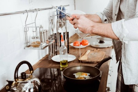 Partial view of young man cooking scrambled eggs o...