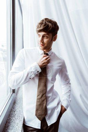 Photo pour Homme d'affaires souriant en chemise blanche attacher cravate cou dans le bureau - image libre de droit