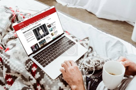 Photo for Cropped image of man holding coffee cup and using laptop with bbc news on screen in bed at home - Royalty Free Image