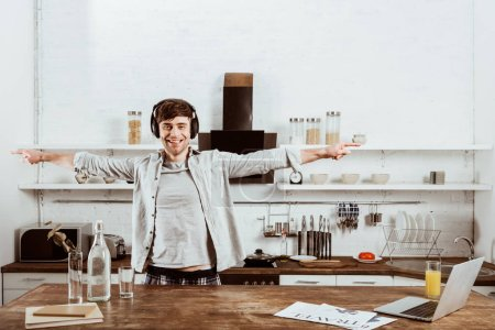 cheerful male freelancer in headphones standing with wide arms near table with laptop in kitchen at home