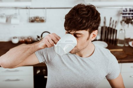 high angle view of man drinking coffee on breakfast in kitchen at home