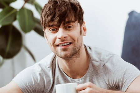 portrait of smiling man looking at camera and drinking coffee at home