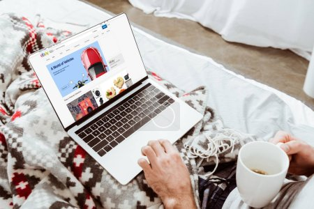 cropped image of man holding coffee cup and using laptop with ebay on screen in bed at home