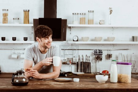 happy young man drinking coffee at table with toasts and coffee pot in kitchen at home