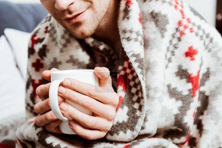 Photo pour Vue partielle de l'homme malade enveloppé dans une couverture assis avec une tasse de thé dans le lit à la maison - image libre de droit