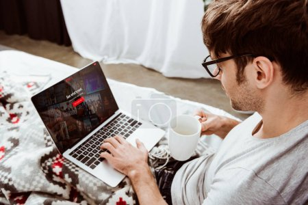 side view of man holding coffee cup and using laptop with netflix on screen in bed at home