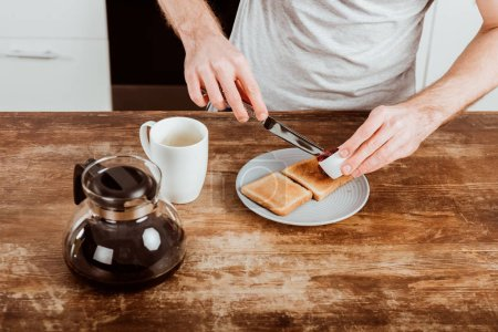 Photo for Cropped image of man spreading toast by jam at table with coffee pot and cup in kitchen - Royalty Free Image