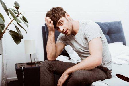 fatigué de jeune homme d'affaires à la recherche à la caméra et assis sur le lit à la maison