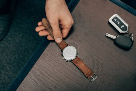 cropped image of businessman taking off watch from table at home