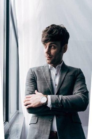 Foto de Empresario joven pensativo en chaqueta mirando lejos en oficina - Imagen libre de derechos